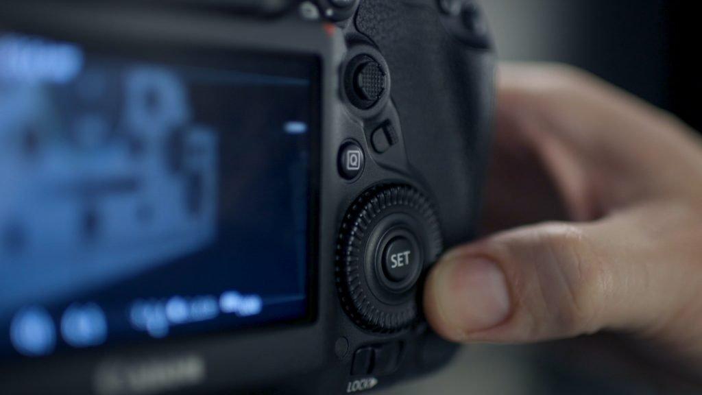 person holding gray digital camera