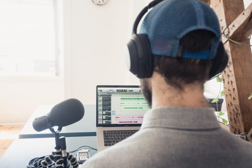 man in gray shirt wearing blue headphones