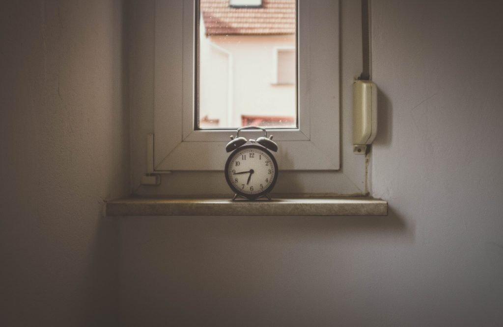 white alarm clock on window still